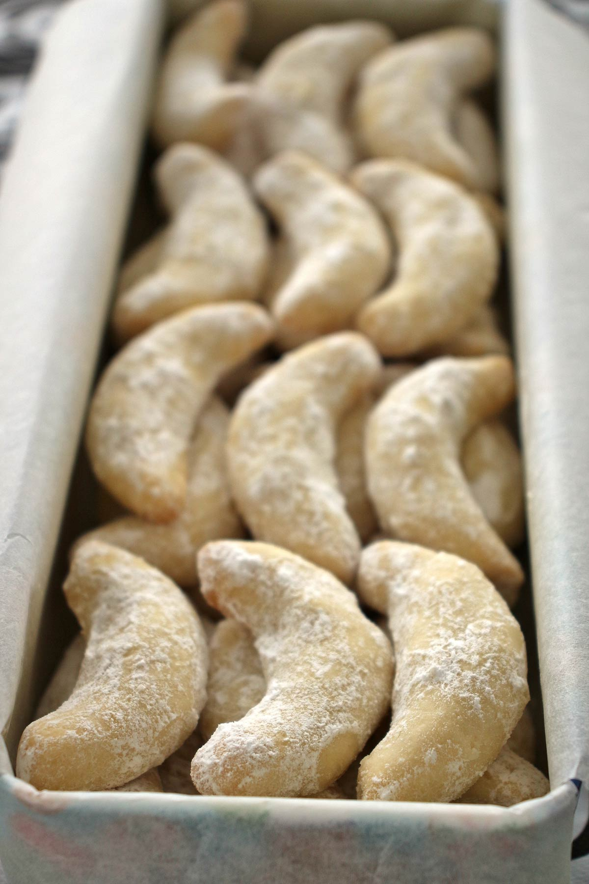 Closeup of a rectangular cookie tin filled with vanilla crescent cookies dusted with powdered sugar.