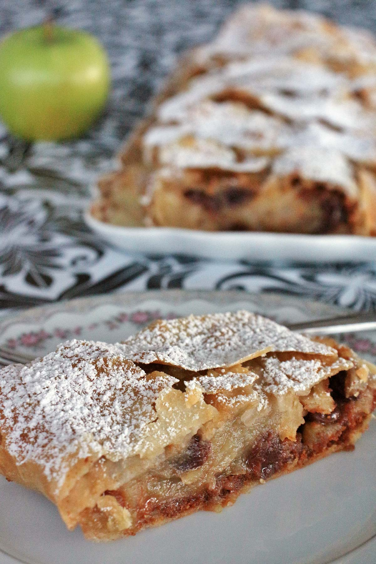 Closeup of a slice of apple strudel on a plate with a platter in the background.
