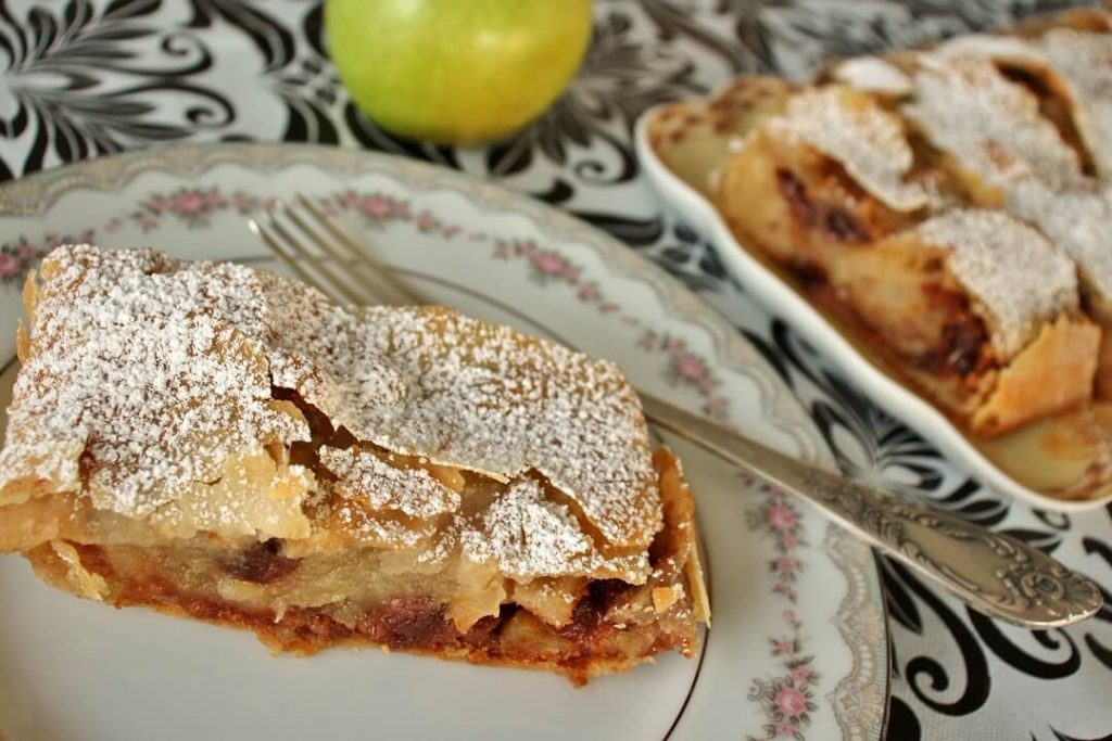 Slice of apple strudel with powdered sugar on a plate