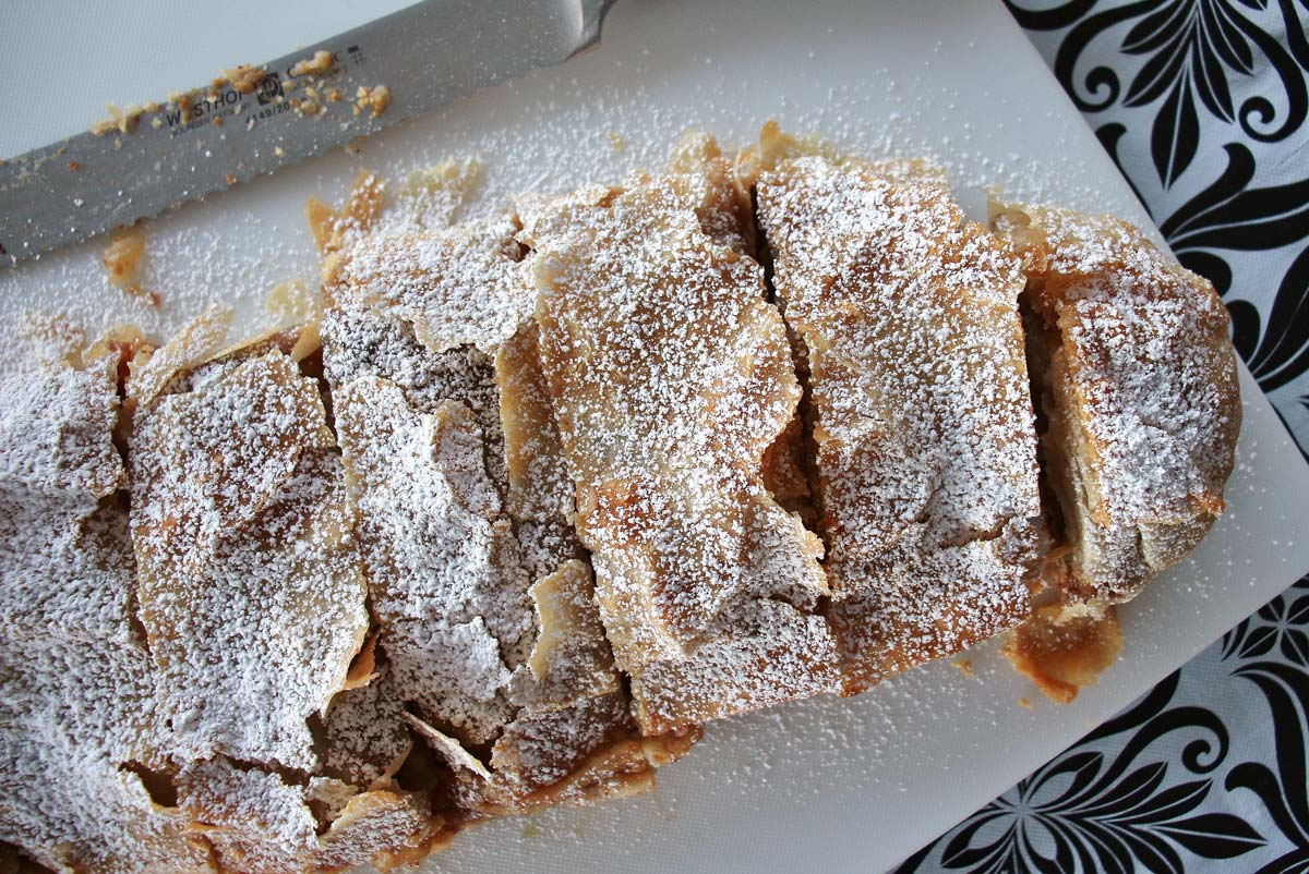 Sliced apple strudel on a cutting board, topped with powdered sugar.