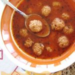 meatball soup in a tomato broth with a spoon lifting out a meatball
