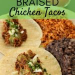 Two braised chicken tacos served with refried black beans and Mexican rice