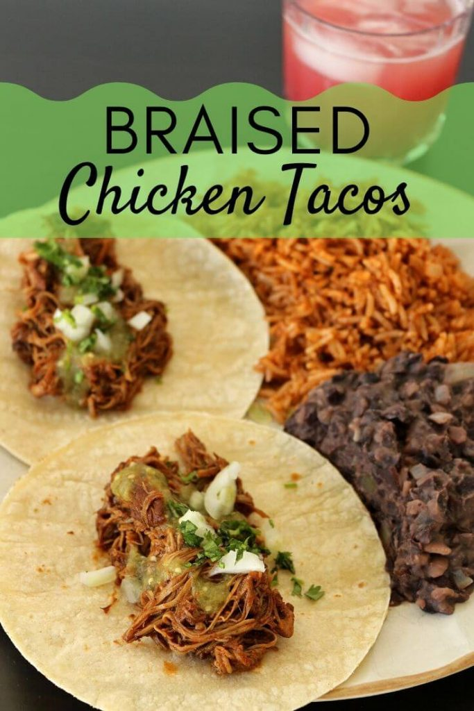 Two braised chicken tacos with salsa verde, cilantro and chopped onion, served with refried black beans and Mexican rice