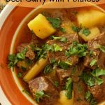 a bowl of beef and potato curry with chopped cilantro sprinkled on top