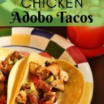 chicken tacos in corn tortillas on a colorful plate with a strawberry drink to the side