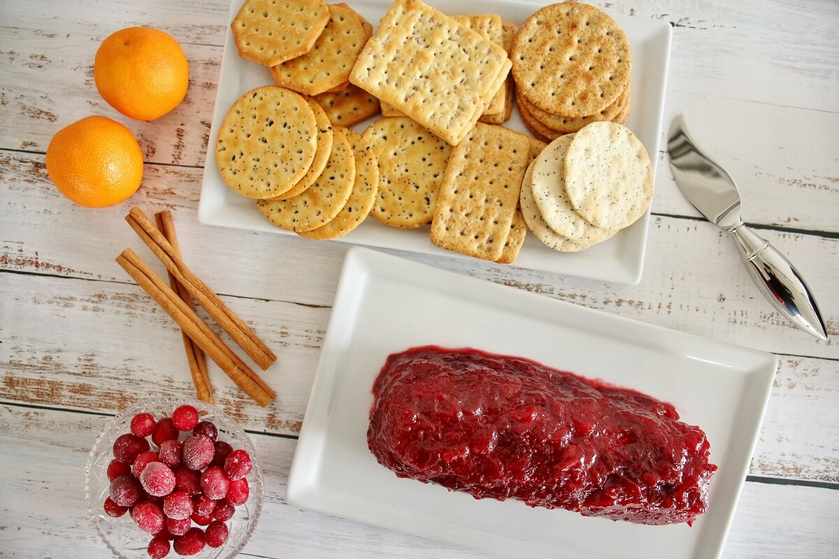A cranberry goat cheese log on a white plate, next to crackers, oranges, cinnamon sticks.