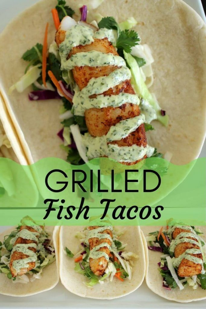 3 grilled fish tacos served on flour tortillas, with slaw beneath the fish, and a light green cilantro mayo drizzled over the top