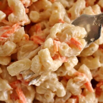 Closeup of a forkful of macaroni salad with grated carrot.