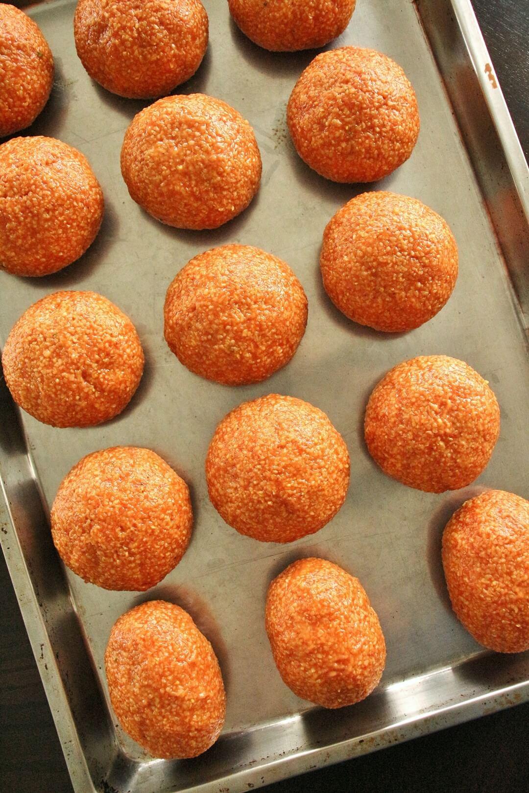 A tray of round ishli koftes with a few oval-shaped koftes