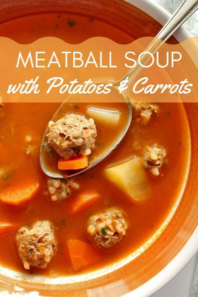 Meatball soup with potatoes and carrots in a bowl, with a spoon holding some soup over the bowl's surface