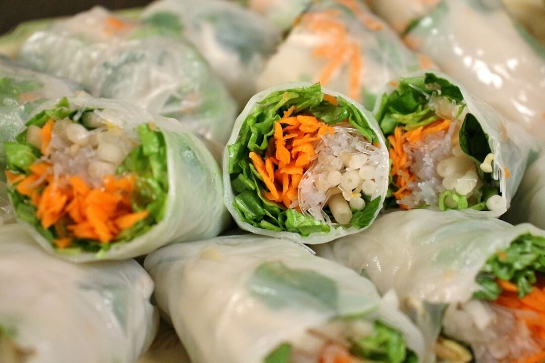 Stacks of nime chow with the cross-sections showing (filled with lettuce, carrots, beansprouts, etc)