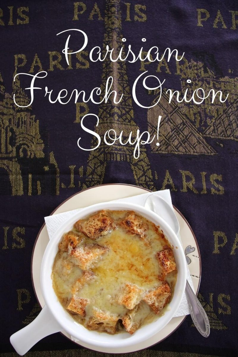 A bowl of French onion soup served on a Parisian scarf with an image of the Eiffel Tower on it