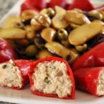 Tuna-stuffed piquillo peppers on a platter with fingerling potato and olive salad