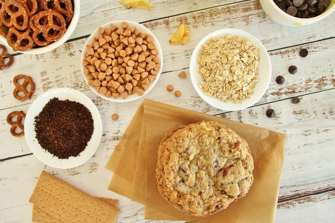 overhead view of compost cookies surrounded by bowls of mix-in ingredients