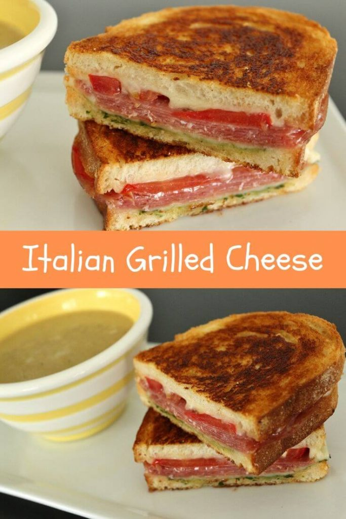 A grilled cheese with salami, tomato, and pesto on a white plate with a cup of soup in a white and yellow striped bowl.
