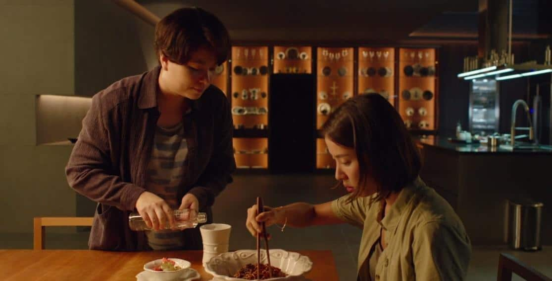 A screenshot from the movie Parasite showing madame eating noodles