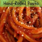 close up of hand rolled pinci pasta in tomato sauce