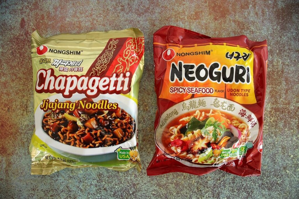 Two packages of Korean instant noodles: Chapagetti in gold packaging and Neoguri in red packaging.