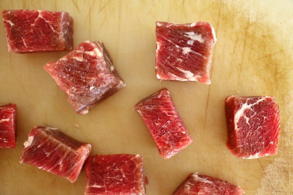 Cubed raw steak on a cutting board