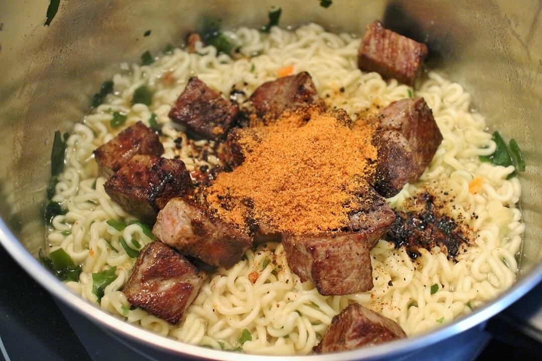 Cooked instant noodles in a saucepan topped with seared beef cubes and seasoning packets.