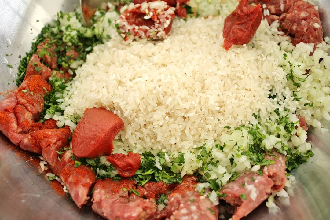 Filling for dolma in a mixing bowl, including ground beef, rice, parsley and tomato paste