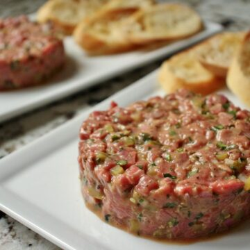 French steak tartare with toasted baguette on white plates