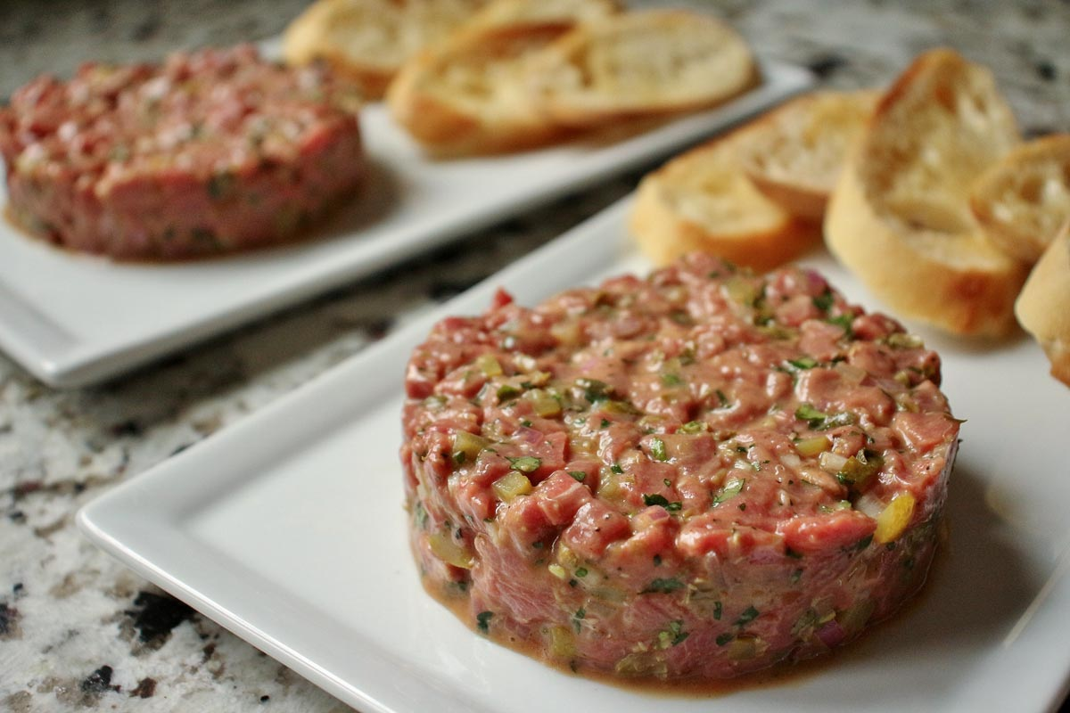 Two servings of steak tartare on white rectangular plates with toasted baguette slices