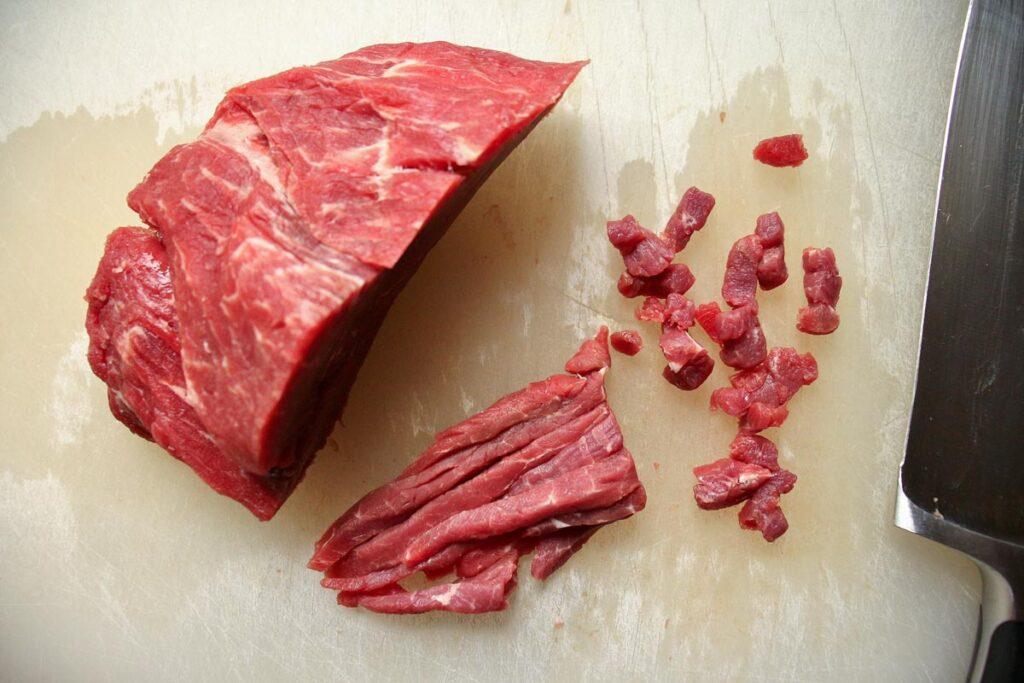 Hand-chopping beef tenderloin on a white cutting board