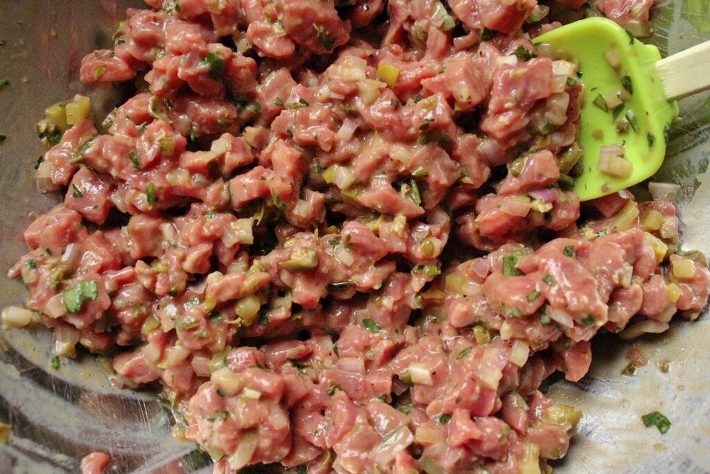 Steak tartare mixture in a metal mixing bowl