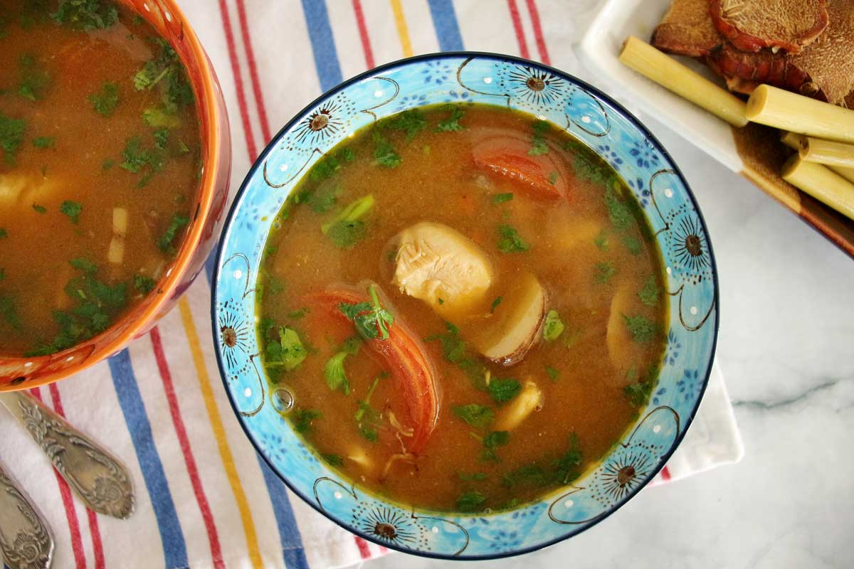 Two colorful bowls of soup on a striped cloth.