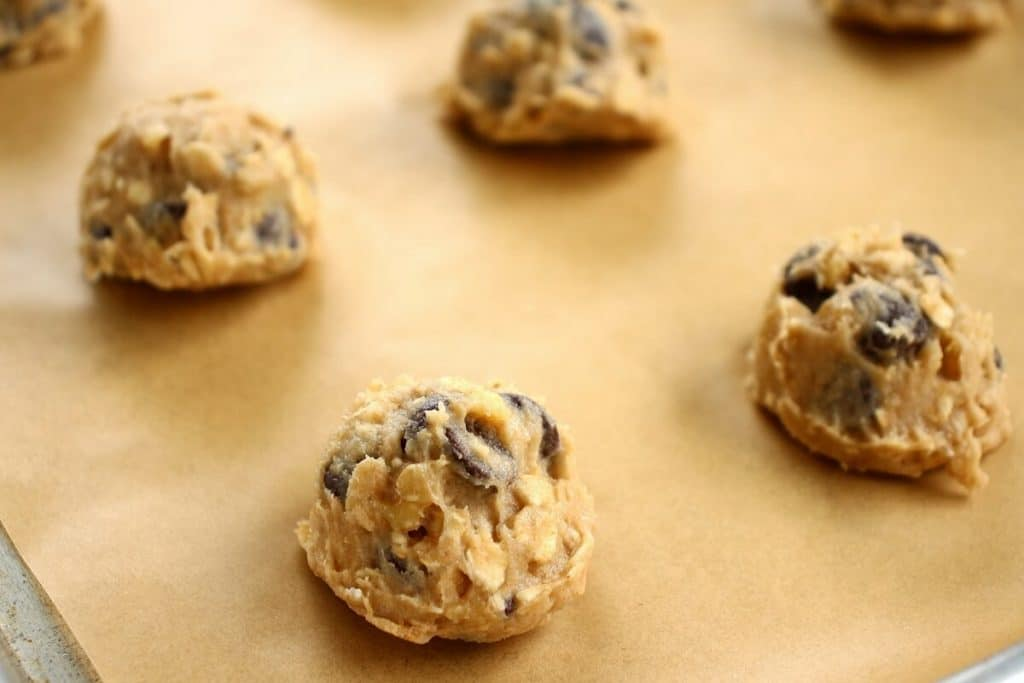 Scooped portions of banana walnut chocolate chip cookies on a parchment-lined baking sheet