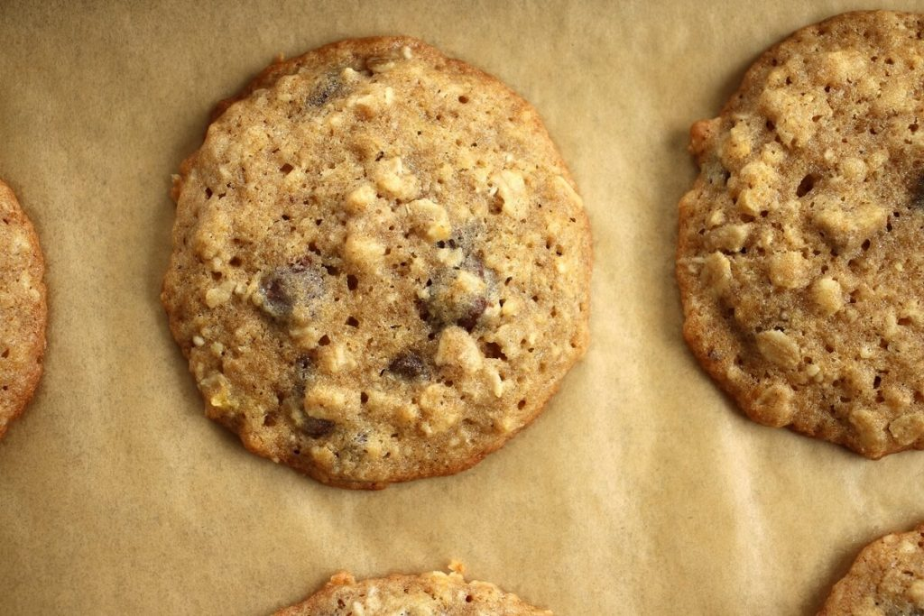 A close up of baked banana oatmeal chocolate chip cookies on a baking sheet