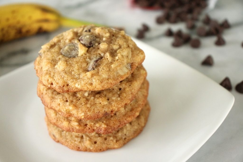 A stack of banana oatmeal chocolate chip cookies on a white square plate with a banana and chocolate chips in the background
