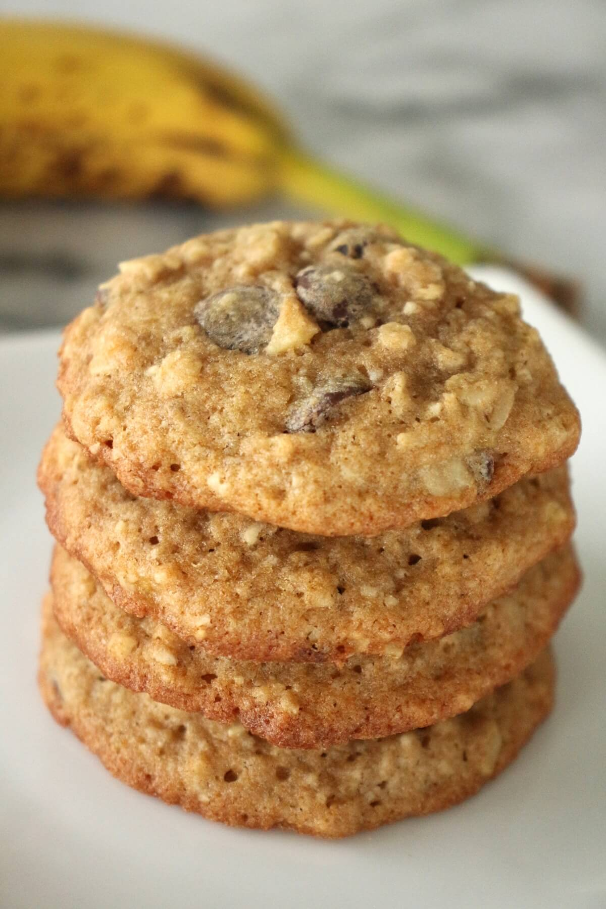A stack of banana walnut chocolate chip cookies on a white square plate with a banana in the background