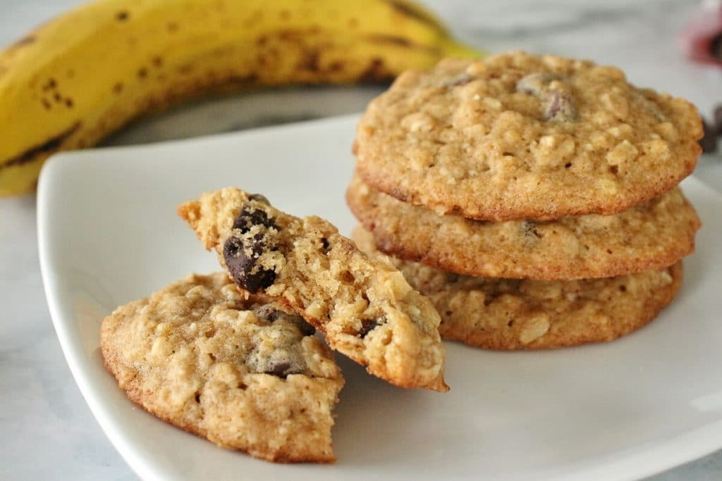 A stack of banana oatmeal chocolate chip cookies on a white square plate with a banana and chocolate chips in the background. One of the cookies is broken in half.