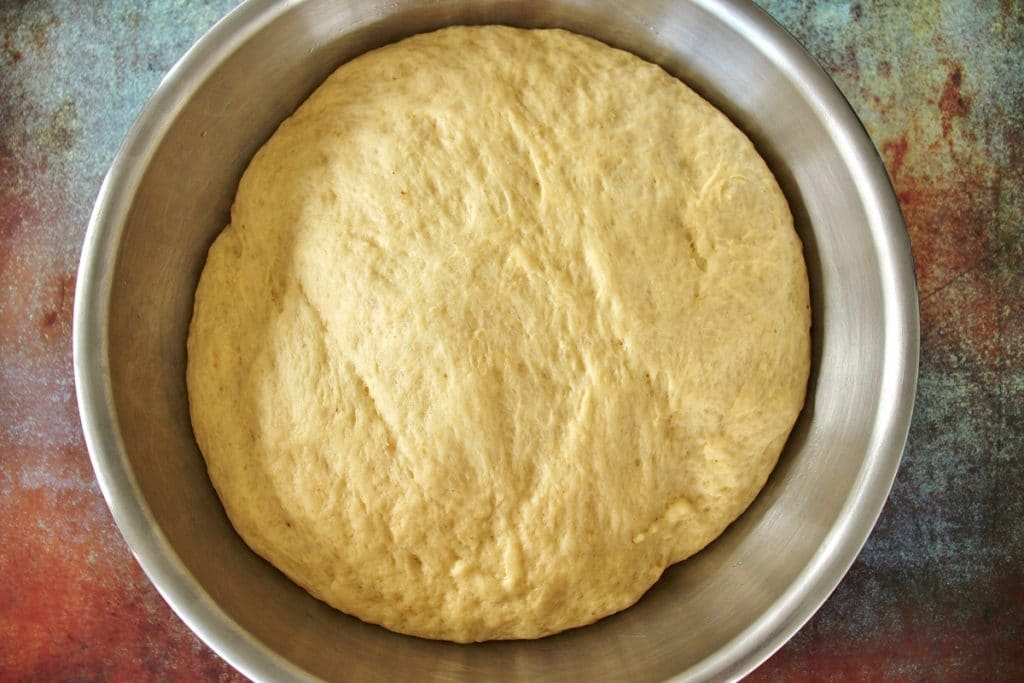 Chorek dough in a large metal mixing bowl after proofing, doubled in size
