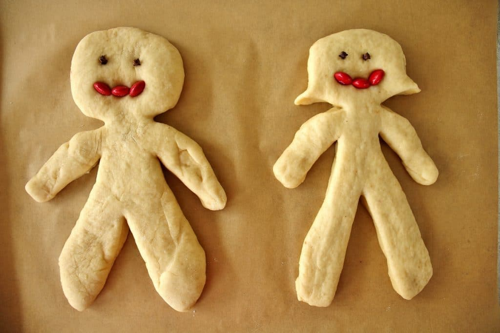 A man and woman chorek person on a parchment lined baking sheet, with whole cloves for eyes and red m&ms for mouths, prior to baking