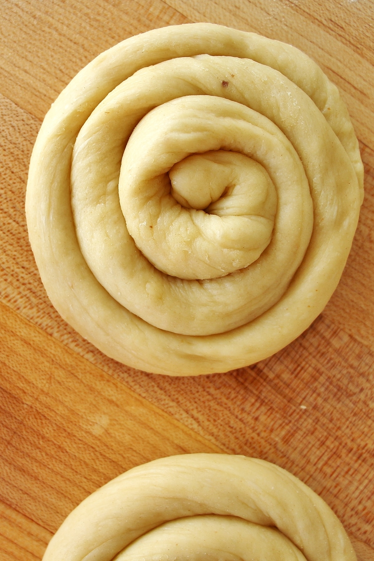 Dough shaped into a spiral or snail shape on a wooden cutting board