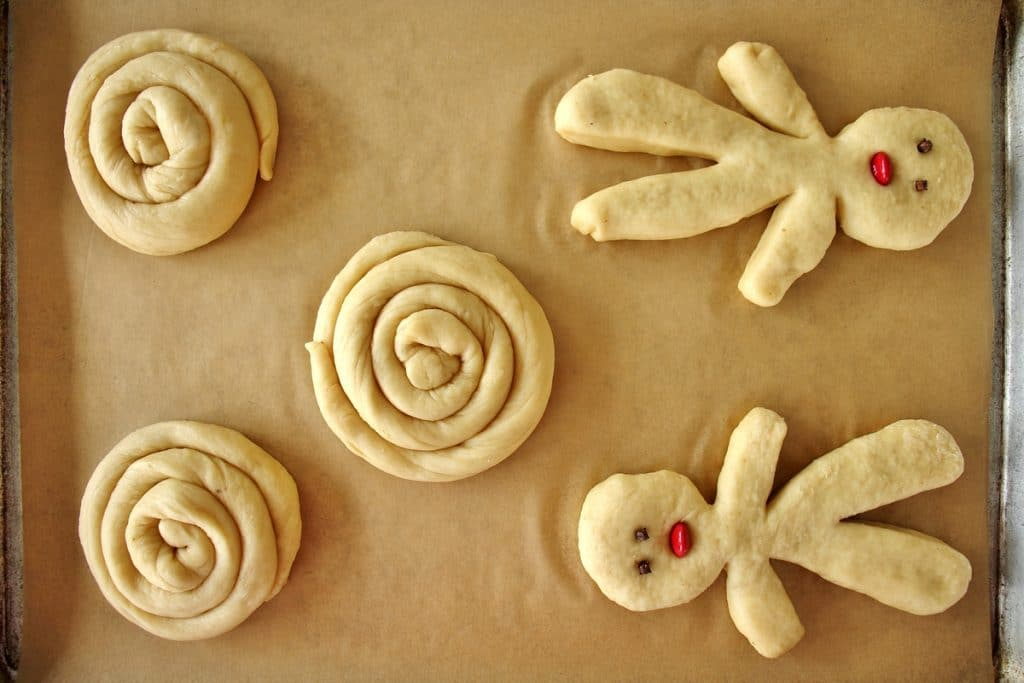 A baking sheet with 3 spiral shaped choreks and 2 small person-shaped choreks, prior to baking