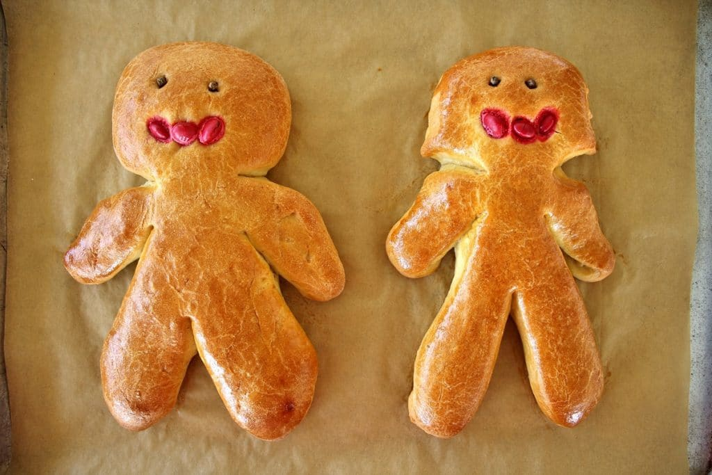 A man and woman chorek person on a parchment lined baking sheet, with whole cloves for eyes and red m&ms for mouths, after baking