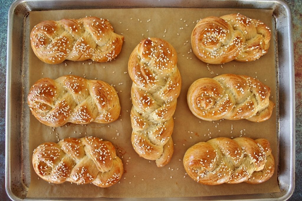 A sheet pan of braided baked choreks topped with sesame seeds
