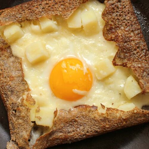 buckwheat galette with egg, potato and cheese in nonstick pan