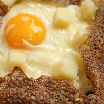 Closeup of a buckwheat galette (crepe) filled with potatoes, cheese, and fried egg