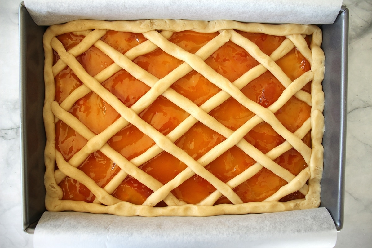 The finished Russian pirog before baking, with a lattice top and apricot jam peeking through