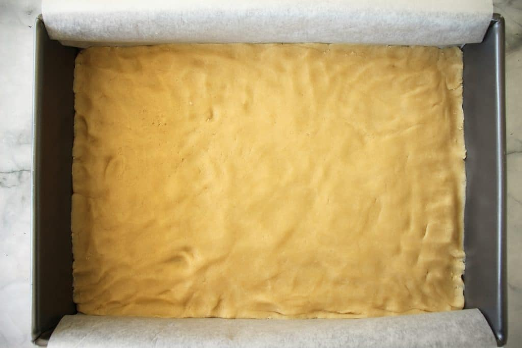 Dough pressed into an even layer in a baking pan