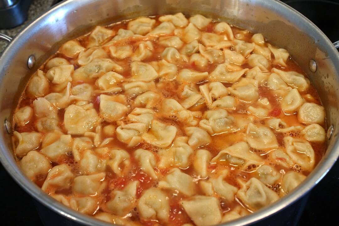 Manti dumplings boiling in a tomato broth in a large stainless steel pot
