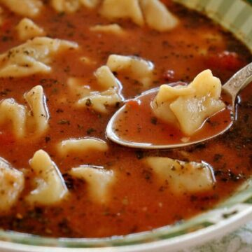Armenian manti soup with dumplings in a tomato broth served in green-rimmed wide bowl