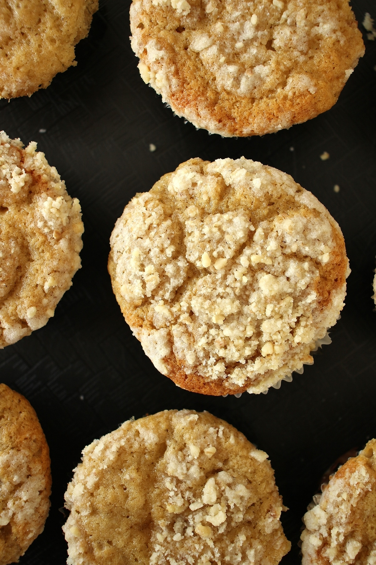 Bakery style banana muffins with streusel topping on a black tray