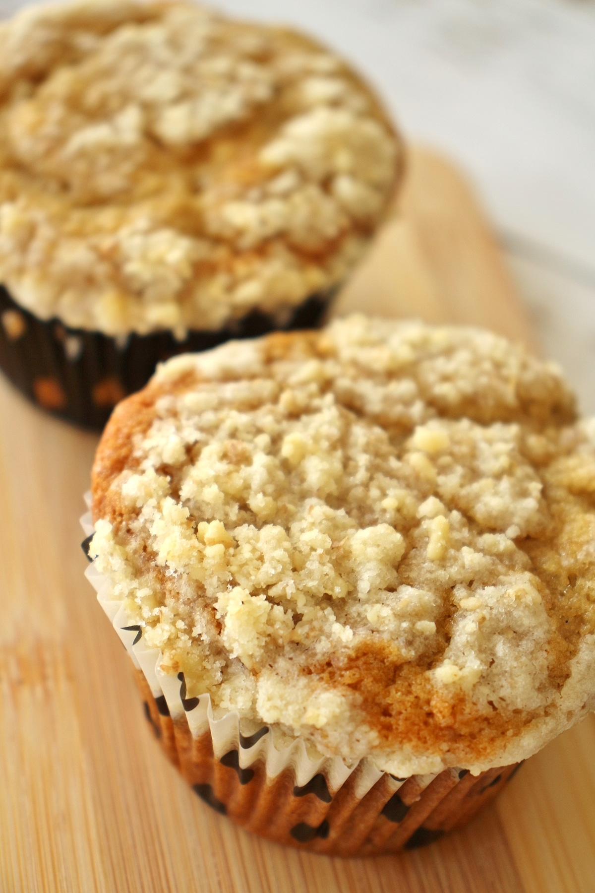 Two bakery style banana muffins on a small wooden board.