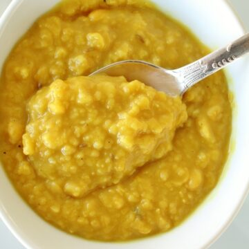 a bowl of yellow chana dal curry with a spoon